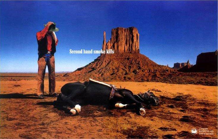 En cowboy står fortvilet ved siden døde hest. Second hand smoke kills.